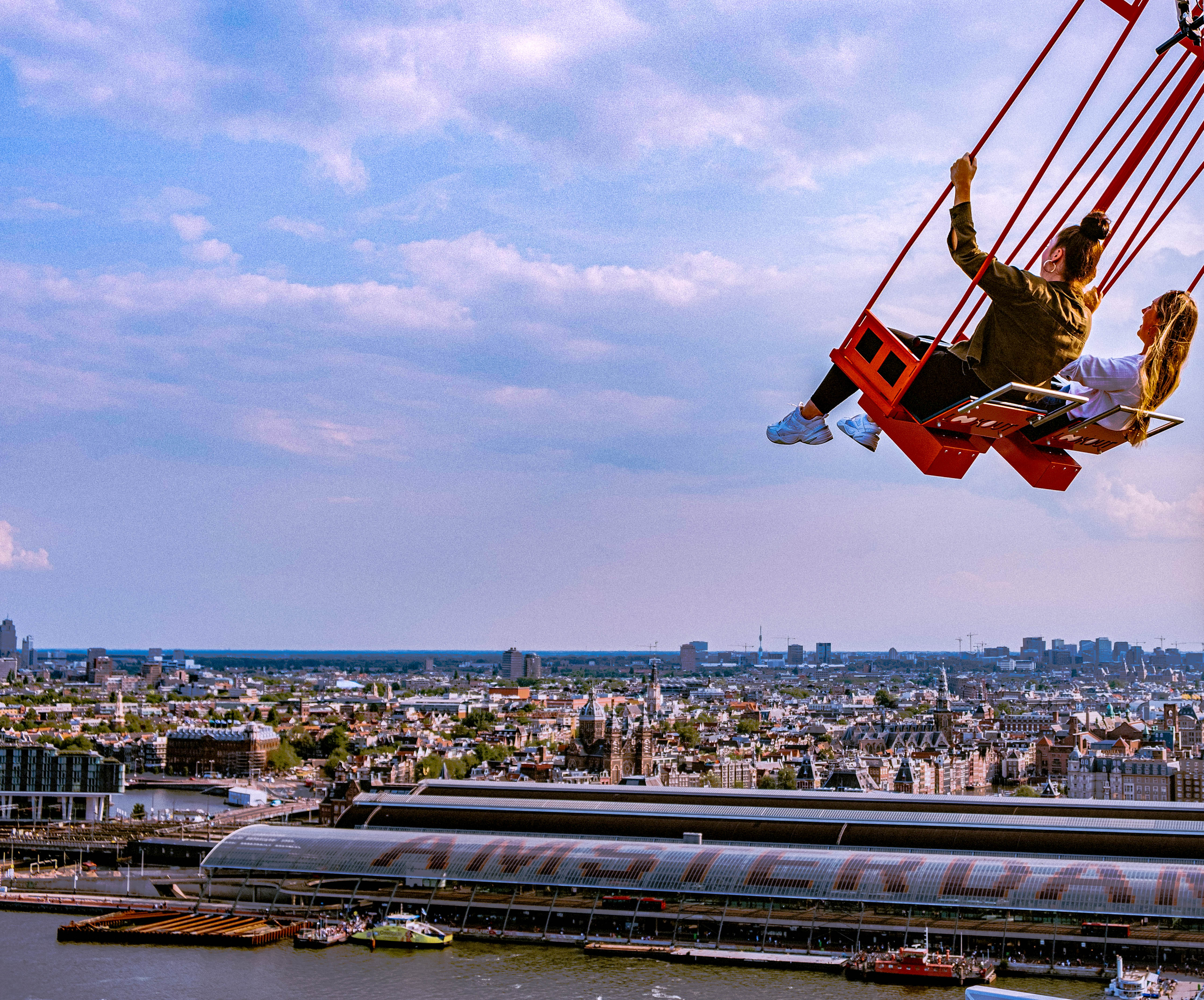 Two women on the A'dam Tower swing with centraal station and the Amsterdam skyline in the background.