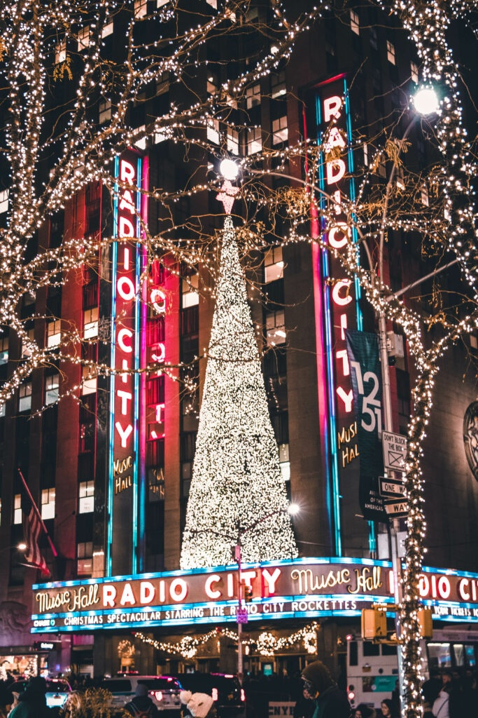 New York's Radio City Music Hall with a light covered Christmas tree on top of its entrance