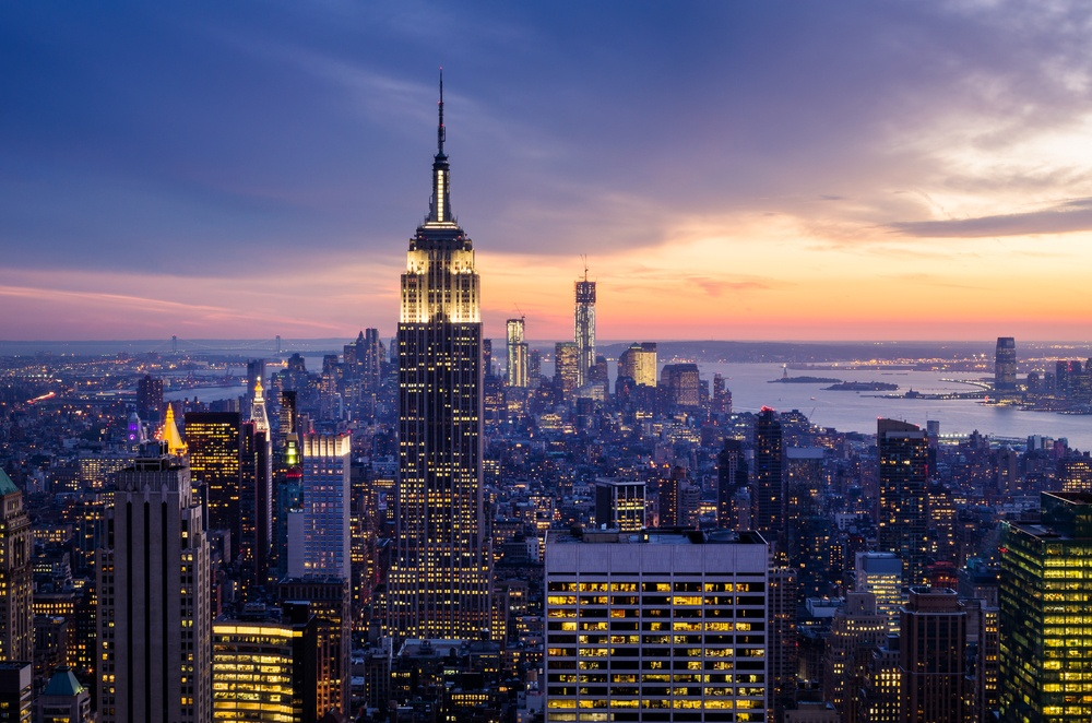 Dusk falls on the New York skyline with the Empire State building front and center and Hudson's Bay in the background