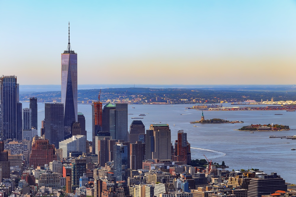 New York's skyline with Liberty Island in the background and One World Trade Center rising above the other buildings