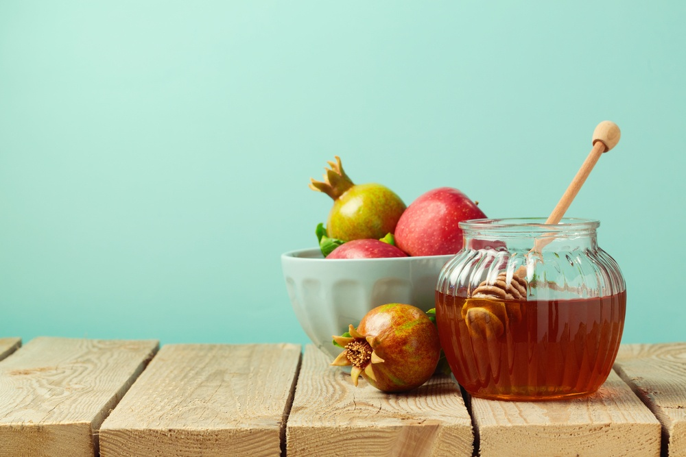 A selection of traditional Hebrew New Year's foods, including apple, pomegranate, and honey