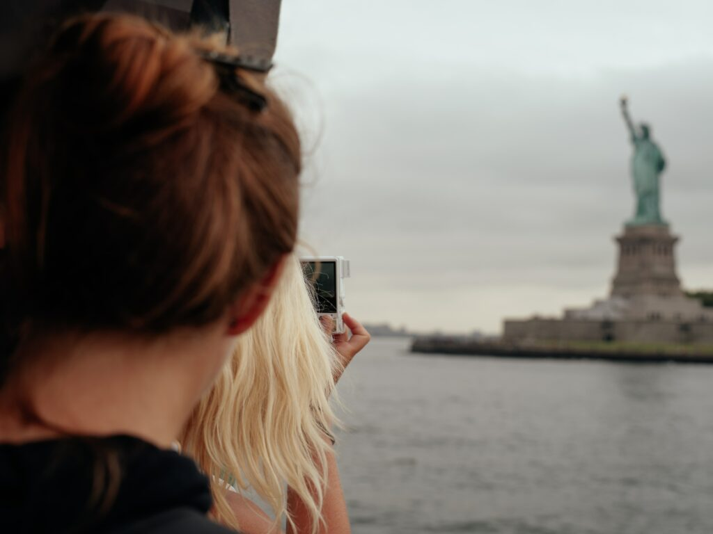 Photo: A woman taking a photo on a Statue of Liberty cruise
