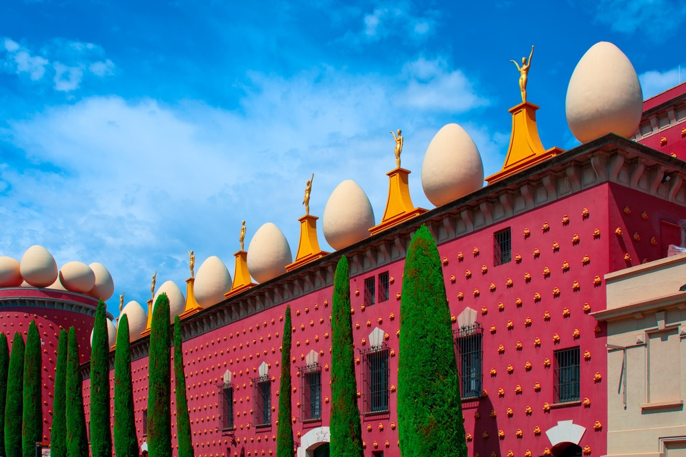The quirky exterior of the Dalí Theater Museum, with eggs, statues, golden bread rolls and cypress trees.