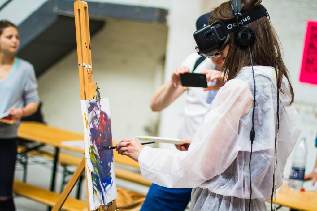 Woman uses virtual reality headset while painting on a canvas