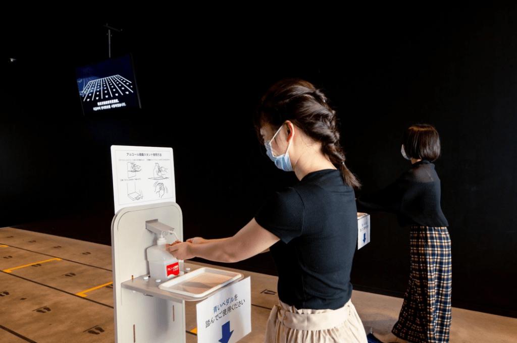 Visitatore giapponese con maschera facciale che disinfetta le mani entrando in un museo