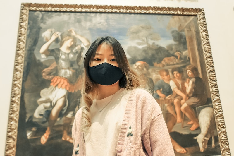 A person wearing a mask in a museum