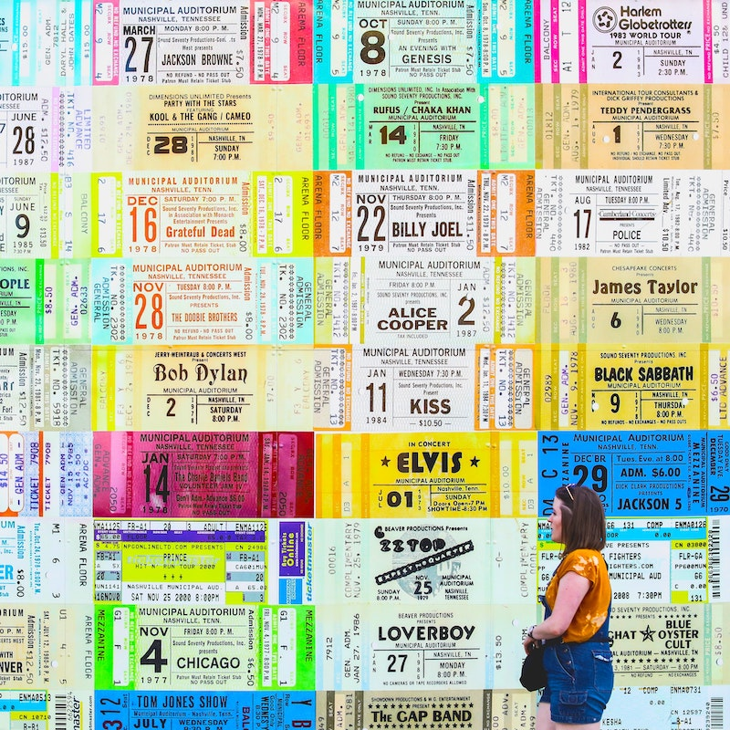 Women walking in front of a wall of tickets