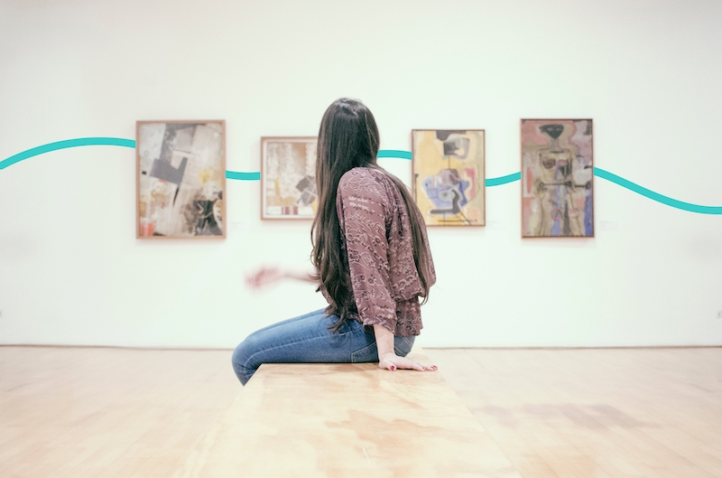 Recapture your visitors' attention. Picture of a girl sitting in front of some paintings.